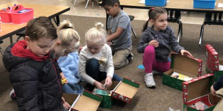 K students packing shoe boxes for Operation Christmas Child